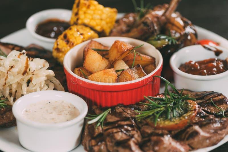 zakończenie widok piec na grillu warzywa, piec kurczaków skrzydła i wołowina stki z grulami na talerzu, obrazy stock