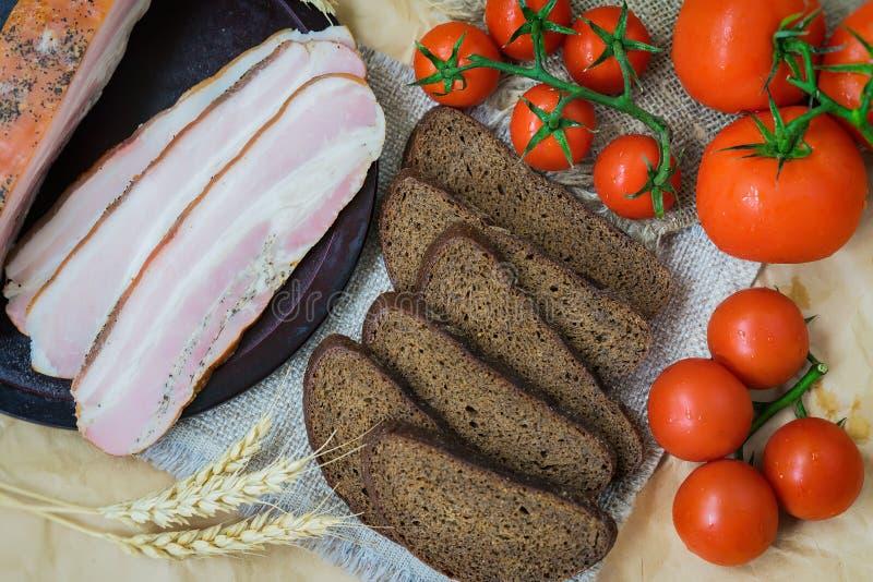 Zakończenie widok plasterki różowy bekon, kawałki żyto chleb, dojrzali czerwoni pomidory świeże żywności organicznej Szybka smako obrazy royalty free