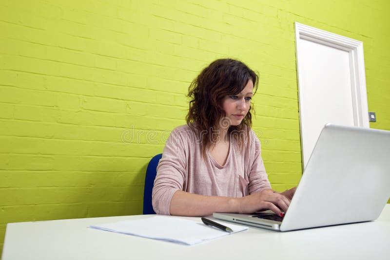 Zakończenie widok pracuje przy jej biurkiem młoda kobieta obraz royalty free