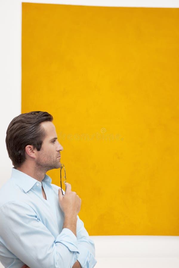 Zakończenie widok rozważny młody człowiek przed ściennym obrazem fotografia royalty free