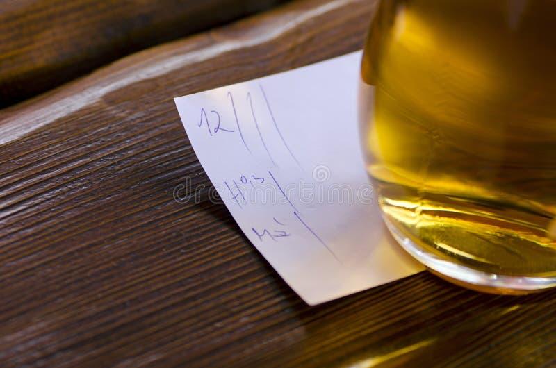 Zakończenie widok szkło piwo z rachunku lying on the beach na stole wewnątrz zdjęcia stock