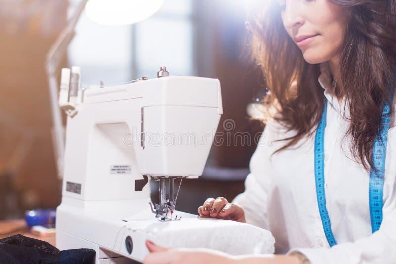 Zakończenie widok szwalna maszyna i potomstwo kobieta dostosowywamy działanie na nim podczas gdy siedzący w warsztacie zdjęcie royalty free