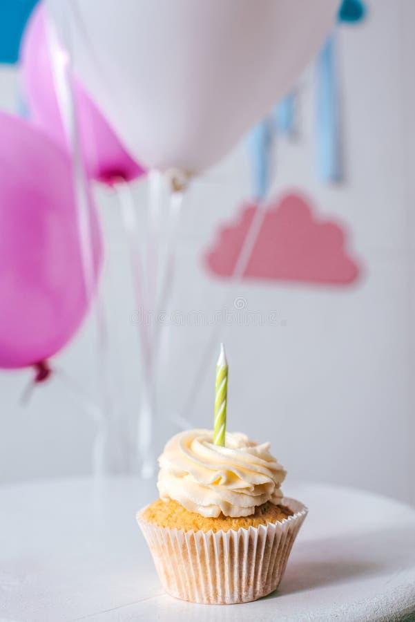 zakończenie widok wyśmienicie babeczka z świeczką i balonami przy przyjęciem urodzinowym obraz royalty free