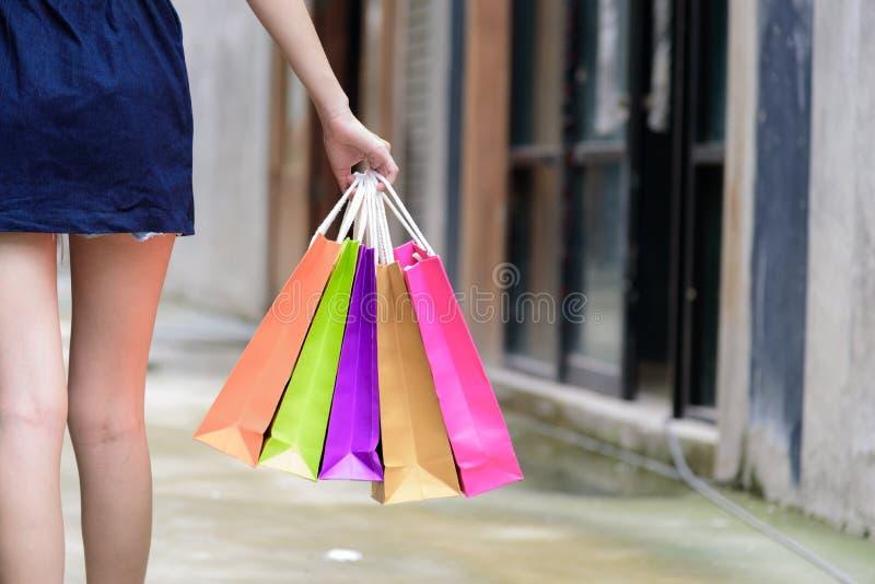 Zakończenie widoku azjatykcia dziewczyna mienia robi zakupy kolorowe torby z zakupy budynku i centrum handlowego tłem zdjęcia royalty free