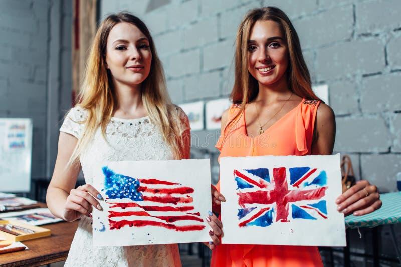 Zakończenie wizerunek dwa młodej kobiety trzyma rysunek Brytyjski i flaga amerykańskie pociągany ręcznie z aquarelle techniką dal zdjęcie royalty free