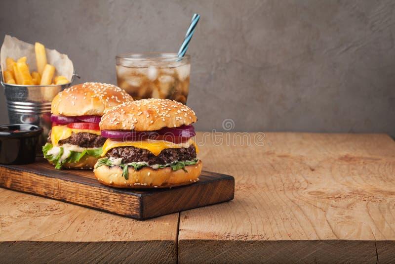 Zakończenie wyśmienicie świeży domowy robić hamburger z sałatą, serem, cebulą i pomidorem na nieociosanej drewnianej desce na cie obrazy stock