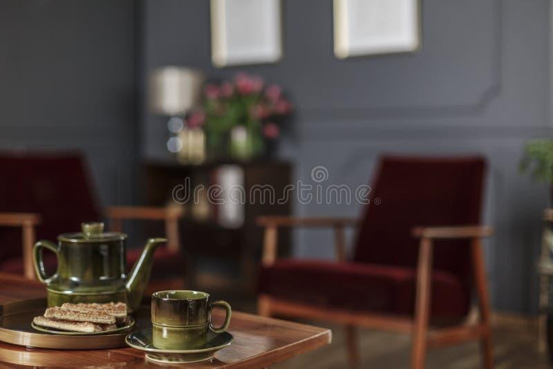 Zakończenie zielony dzbanek, herbaciana filiżanka i ciastka umieszczający na stole w th, zdjęcie stock