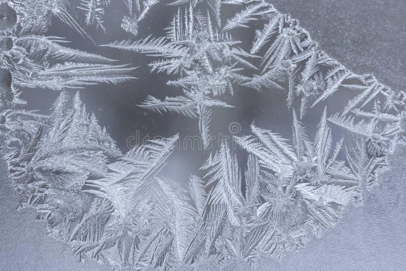 Zakończenie zimy mroźny wzór z elongated śpiczastymi płatkami śniegu na okno zdjęcia stock
