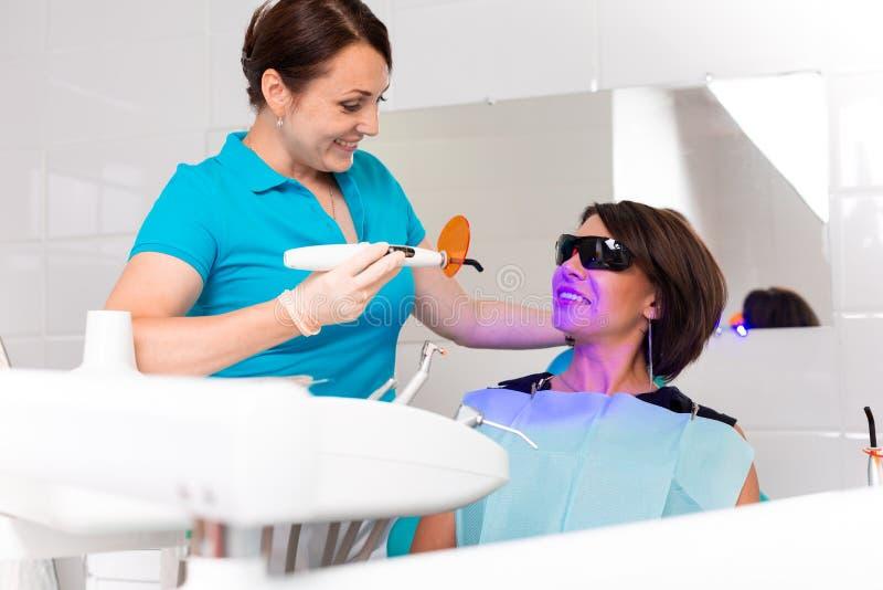 Zako?czenie portret ?e?ski pacjent przy dentyst? w klinice Z?by bieleje procedur? z pozafioletowego ?wiat?a ULTRAFIOLETOW? lamp? fotografia royalty free