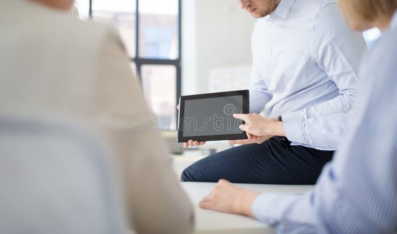 Zako?czenie up biznes dru?yna z pastylka komputerem osobistym przy biurem zdjęcia royalty free