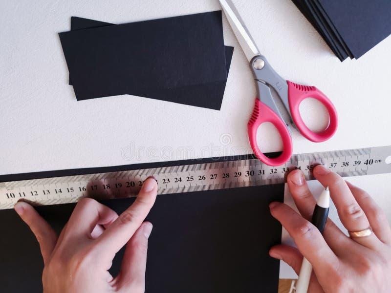 Zako?czenie up strzela? - fachowej kobiety decorator, projektant pracuje z Kraft papierem i robi kopercie przy warsztatem, studio zdjęcia royalty free