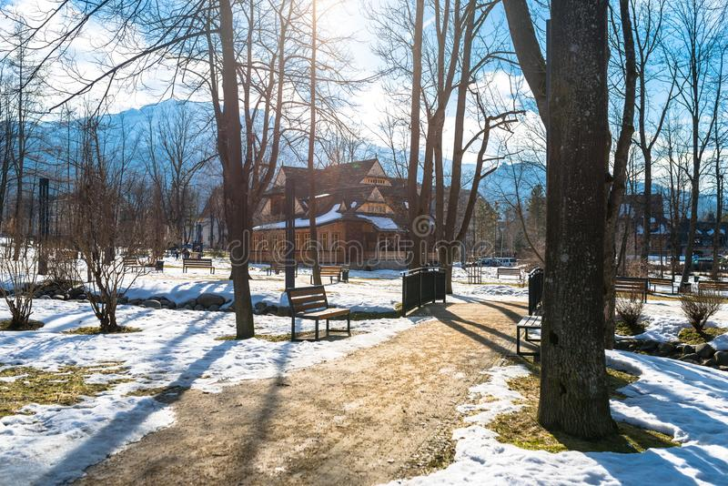 Zakopane, Polônia - 21 de fevereiro de 2019 Parque na cidade coberta com a neve com uma casa de madeira bonita Árvores visíveis,  fotos de stock royalty free