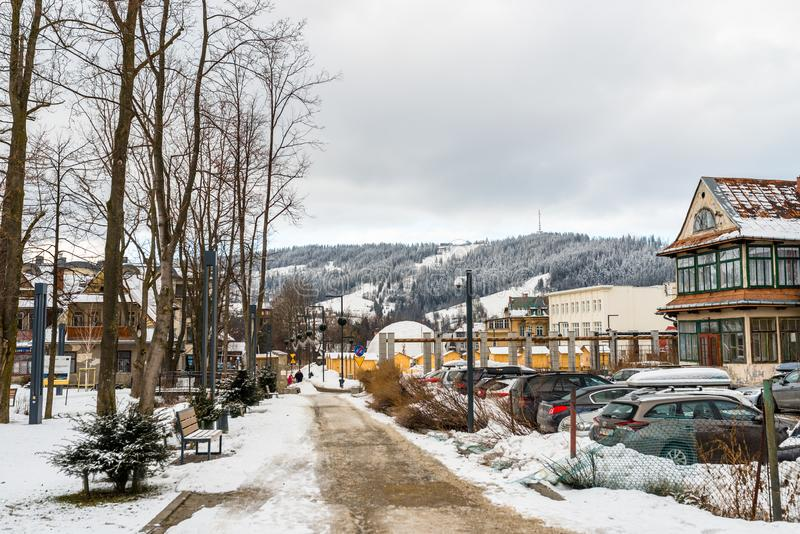 Zakopane, Poland - February 22, 2019. Park in the city covered with snow, visible sidewalk, cars in the parking lot and urban buil royalty free stock image