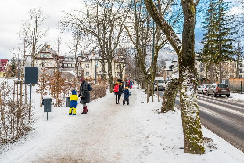 Zakopane, Poland - February 22, 2019. Tourists with small children walking along a snowy road, visible cars, trees and town buildi royalty free stock photography
