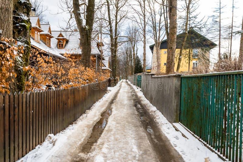 Zakopane, Pologne - 22 février 2019 Rue étroite couverte de la glace et de neige sur la maison en bois évidente gauche et barrièr image libre de droits