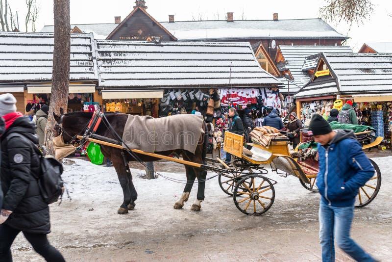 Zakopane, Polonia - 21 de febrero de 2019 Carro del caballo, colocándose en la calle de Krupowki en Zakopane imagen de archivo