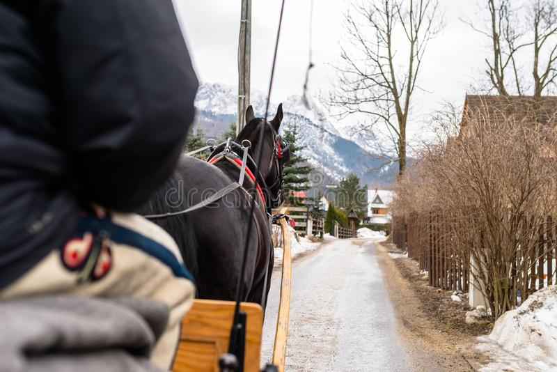 Zakopane, Polonia - 21 de febrero de 2019 Foto de un carro del caballo que monta a través de las calles de la ciudad de Zakopane fotos de archivo libres de regalías
