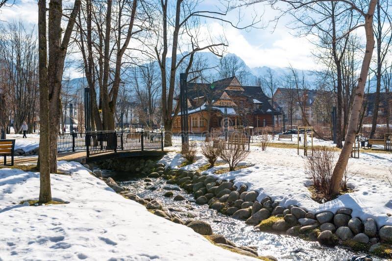 Zakopane, Polonia - 21 de febrero de 2019 Parque en la ciudad cubierta con nieve con una casa de madera hermosa Árboles visibles, foto de archivo