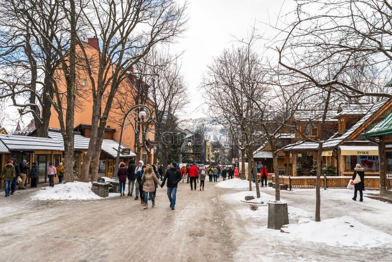 Zakopane, Polonia - 22 febbraio 2019 Una folla della gente sta camminando lungo la via di Krupowki un giorno di inverno La via di fotografia stock libera da diritti