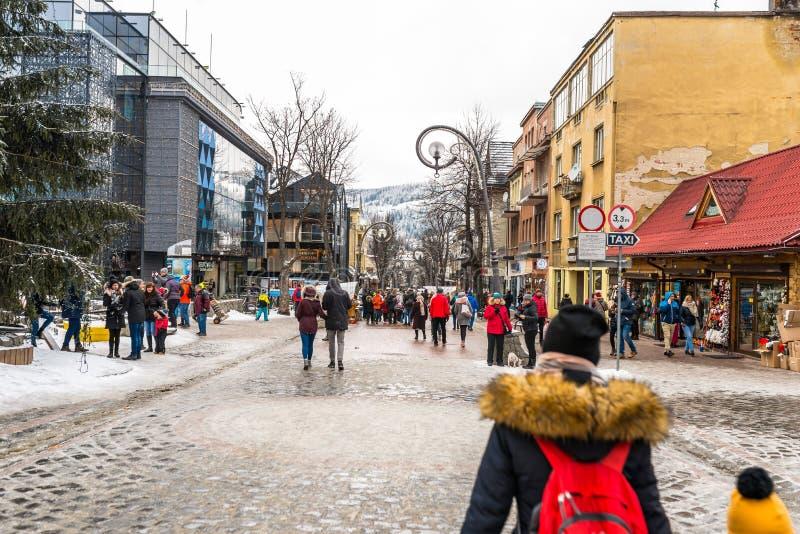 Zakopane, Polonia - 22 febbraio 2019 Una folla della gente sta camminando lungo la via di Krupowki un giorno di inverno La via di fotografie stock libere da diritti