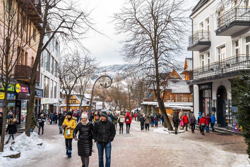 Zakopane, Polonia - 22 febbraio 2019 Una folla della gente sta camminando lungo la via di Krupowki un giorno di inverno La via di immagine stock