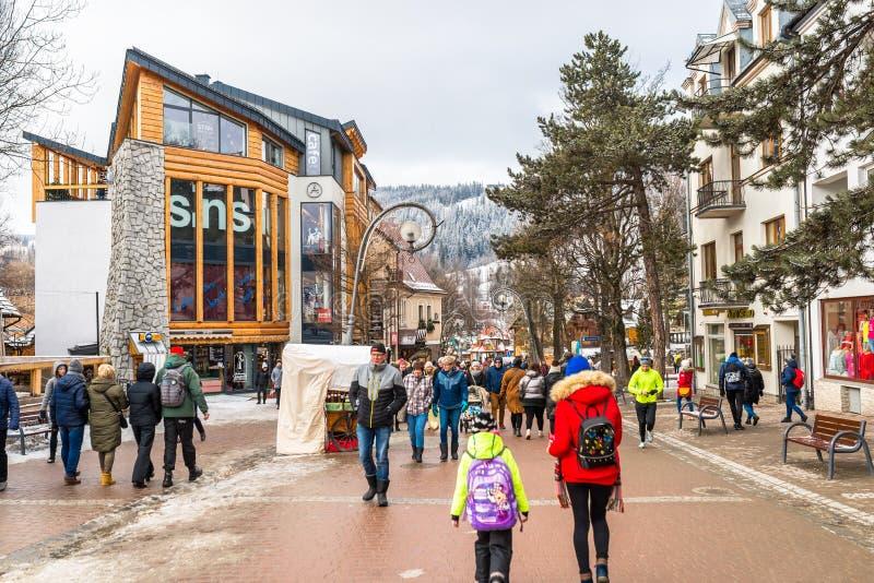Zakopane, Polonia - 22 febbraio 2019 Una folla della gente sta camminando lungo la via di Krupowki un giorno di inverno La via di immagine stock libera da diritti