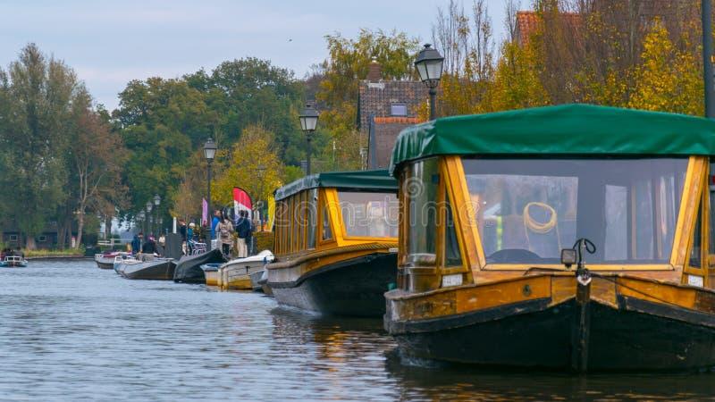 Zakrywać łodzie na wodnych kanałach w Giethoorn holandiach i drzewach na spadku dniu, fotografia stock