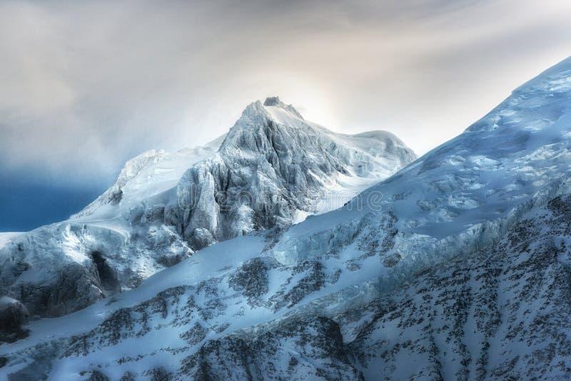zakrywający wysokich gór śniegu wierzchołek Zim góry na jaskrawym słonecznym dniu Alps góry krajobraz z chmurnym niebem zdjęcia stock