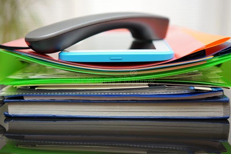 Zaktelefoon en tabletcomputer bovenop de dossiers en de omslagen acc royalty-vrije stock foto