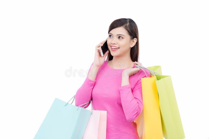 Zakupy azjatykcia kobieta z telefonem komórkowym na białym tle zdjęcie stock