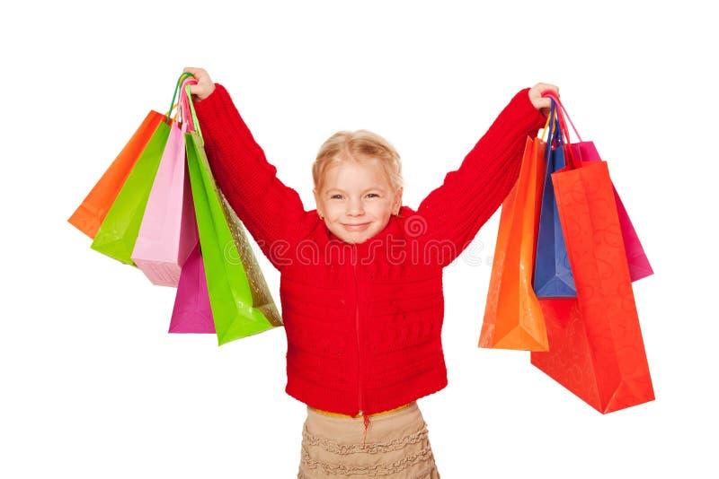 Zakupy dziecko. Szczęśliwa mała dziewczynka trzyma up torba na zakupy. zdjęcie royalty free
