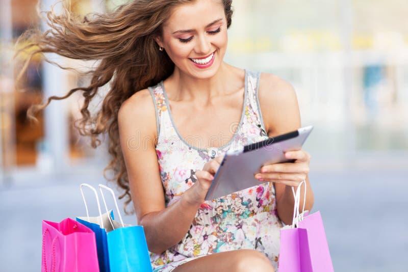 Zakupy kobieta używa cyfrową pastylkę obrazy royalty free