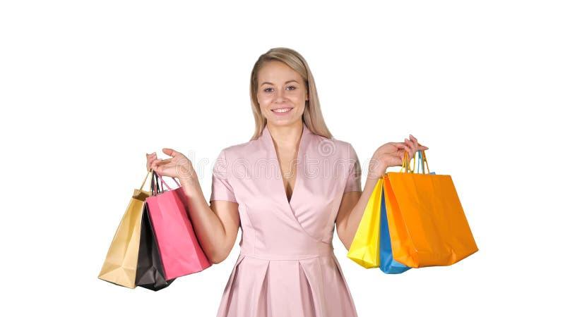 Zakupy kobiety mienia szczęśliwych uśmiechniętych toreb na zakupy iwhile odprowadzenie na białym tle zdjęcia stock