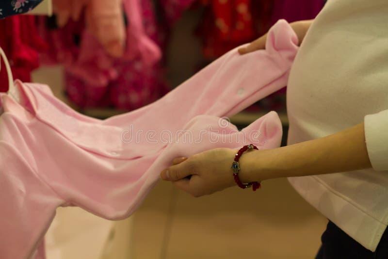 Zakupy młoda kobieta, ręczne viewing stojaka menchie nadaje się dla nowonarodzonej dziewczyny w sklepie zdjęcie royalty free