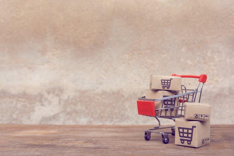Zakupy pojęcie: Kartony lub Papierowi pudełka w wózku na zakupy na brązu drewna stole online zakupów konsumenci mogą robić zakupy zdjęcie stock