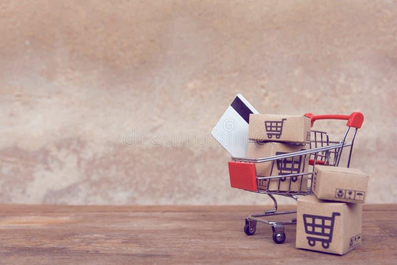 Zakupy pojęcie: Kartony lub Papierowi pudełka w wózku na zakupy na brązu drewna stole online zakupów konsumenci mogą robić zakupy obraz royalty free