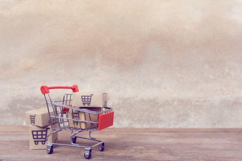 Zakupy pojęcie: Kartony lub Papierowi pudełka w wózku na zakupy na brązu drewna stole online zakupów konsumenci mogą robić zakupy fotografia stock