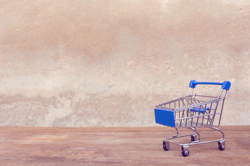 Zakupy pojęcie: Opróżnia błękitnego wózek na zakupy na brązu drewna stole online zakupów konsumenci mogą robić zakupy od domowej  obrazy stock