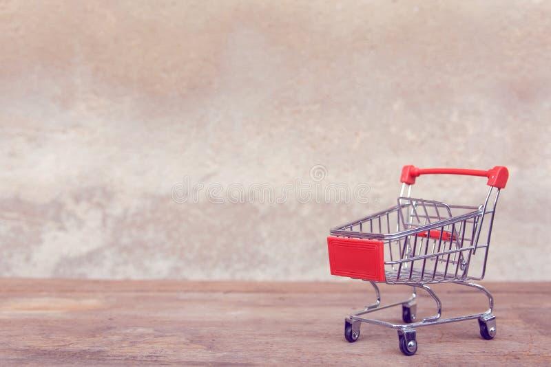 Zakupy pojęcie: Pusty czerwony wózek na zakupy na brązu drewna stole online zakupów konsumenci mogą robić zakupy od domowej i dor obraz stock