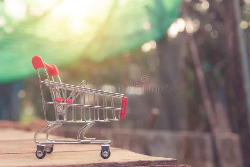 Zakupy pojęcie - Pusty czerwony wózek na zakupy na brązu drewna stole online zakupów konsumenci mogą robić zakupy od domowej i do obrazy royalty free