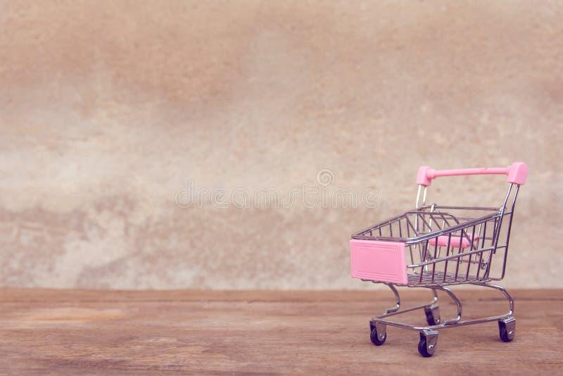 Zakupy pojęcie: Pusty różowy wózek na zakupy na brązu drewna stole online zakupów konsumenci mogą robić zakupy od domowej i doręc zdjęcia stock
