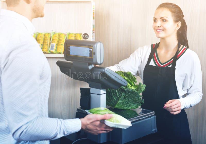 Zakupy pomocniczy pomaga klient ważyć kapusty zdjęcia royalty free