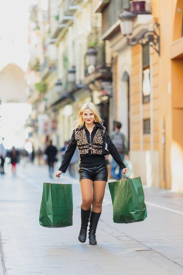 Zakupy, sprzedaż Piękna młoda blondynki dziewczyna z dwa zielonego papieru pakunkami zdjęcia stock