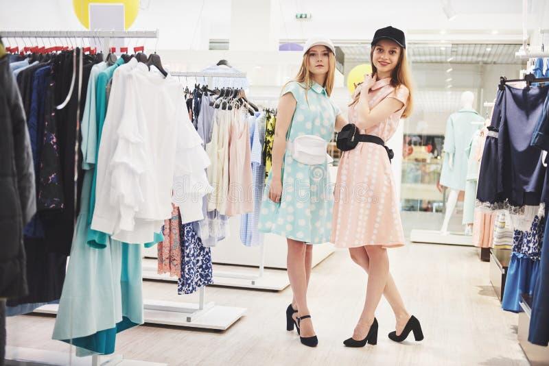 Zakupy terapia w akci Tylni widok dwa pięknej kobiety patrzeje each inny z uśmiechem z torbami na zakupy podczas gdy zdjęcie royalty free