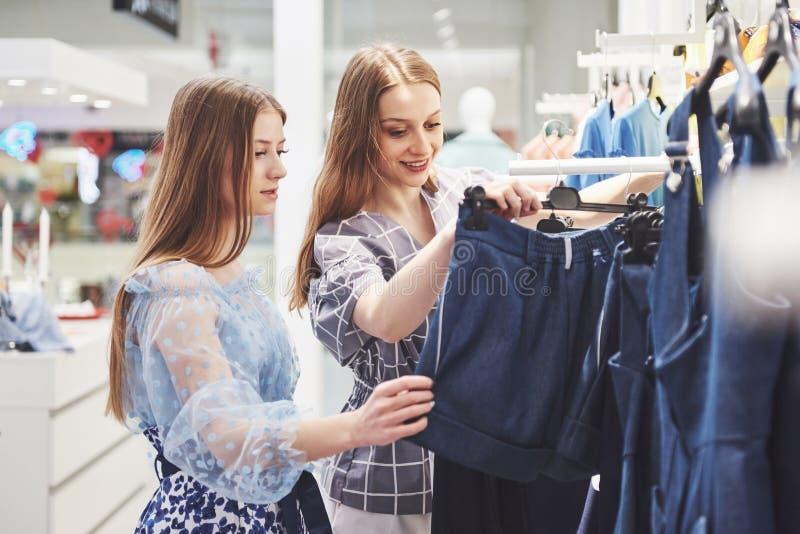 Zakupy terapia w akci Tylni widok dwa pięknej kobiety patrzeje each inny z uśmiechem z torbami na zakupy podczas gdy obrazy royalty free