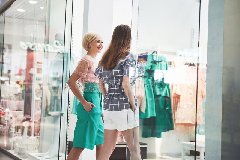 Zakupy terapia w akci Tylni widok dwa pięknej kobiety patrzeje each inny z uśmiechem z torbami na zakupy podczas gdy obraz royalty free