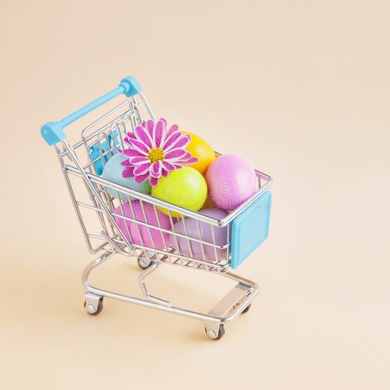 Zakupy tramwaj z barwionymi jajkami i kwiatem zdjęcia royalty free