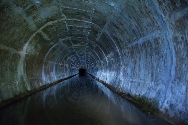 Zalewający wokoło ściekowego tunelu odbija w wodzie fotografia stock