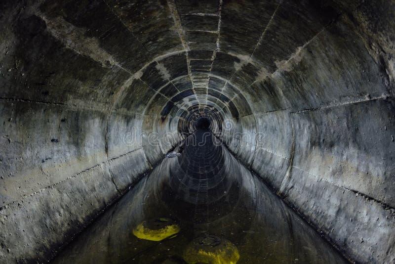 Zalewający wokoło podziemnego drenażowego ściekowego tunelu odbija w brudnej kanalizacyjnej wodzie zdjęcia stock