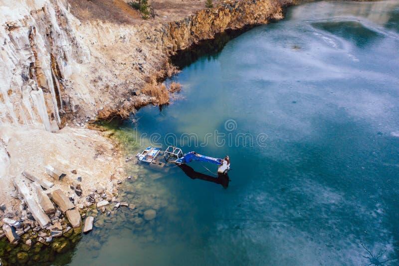 Zalewaj?cy ekskawator w wielkim jeziorze blisko basaltic ?upu zdjęcia royalty free